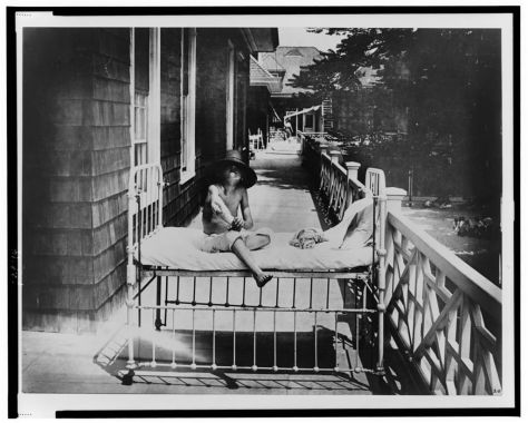 [Tubercular child seated on bed, outdoors, at Sea Breeze Hospital, Coney Island, New York] [between 1900 and 1920]