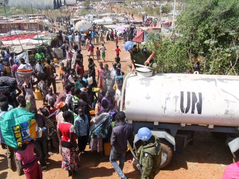 Officers from the UNMISS Japanese contingent providing water to civilians that seek refuge in UN House, the UNMISS compound on the Southwestern outskirts of Juba. UN Photo/UNMISS