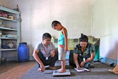 Health workers measure and record the height and weight of Erlan Bernoupereinev, 3, at his home, in Kindik Uzyak Village in the Konlikul District, Republic of Karakalpaksta