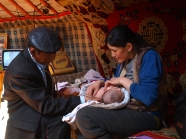 A Community Health Doctor delivers vaccines to a mother and her newborn babies.