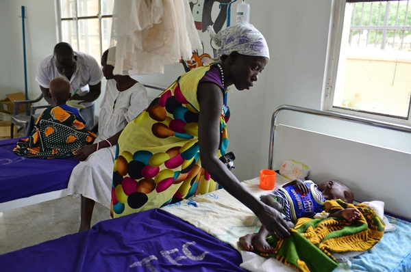 """Country: South Sudan Year: 2014 Photographer: Christine Nesbitt title / Job name:  caption:      On 11 August, Nyabol Hion holds her 2-year-old daughter, Nyanmot Lam, at Al Sabbah Paediatric Hospital in Juba, the capital. """"I travelled here by boat with my husband's brother,"""" says Ms. Hion. """"My three other children stayed with my husband in Walyar in Unity State."""" Her home was destroyed during the conflict, and she lived for a while in the bush after fleeing the fighting. Nyanmot's illness began in April 2014, but she has been in hospital for only three days, receiving therapeutic milk every two hours for her malnutrition, as well as antibiotics to treat her diarrhoea and vomiting. """"Nyanmot is not the only sick child I've seen,"""" say Ms. Hion. """"Many children are sick, and many are passing away."""" After Nyanmot's treatment, they will return to Walyar. """"My wish is for a good life and peace,"""" says Ms. Hion, who advises mothers that """"if your child is sick, take the child to the hospital."""" In early August 2014 in South Sudan, 1.1 million people have been displaced since resurgent conflict erupted in mid-December 2013. An estimated 588,222 of the displaced are children. Some 434,000 people have also sought refuge in neighbouring countries. UNICEF has appealed for US$151.7 million to cover emergency responses across the vital areas of nutrition; health; water, sanitation and hygiene; protection; education; multi-sector refugee response; and cholera response. By 5 August, 62 per cent remained unfunded."""