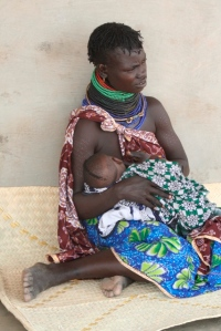 A Turkana mom breastfeeding her child as she waits to be served at a local health center.