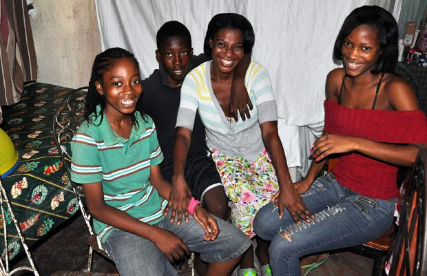 Adeline Eliazard and her three children, Jerry Andrice, Ernst Andrice, and Nadine Andrice (left to right) in their concrete home. (©2014 Jean-Wickens Merlone/World Vision)