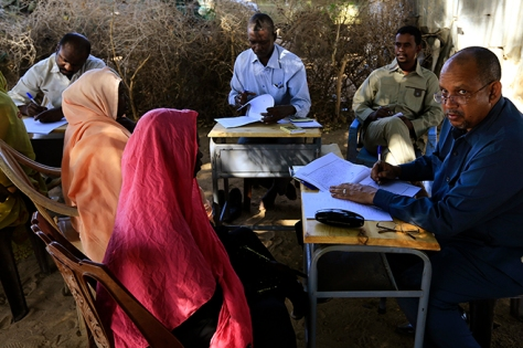 Special Prosecutor for Crimes in Darfur Yasir Ahmed Mohamed (R) and his team talk to women during an investigation into allegations of mass rape in the village of Tabit, in North Darfur, November 20. © 2014 Reuters