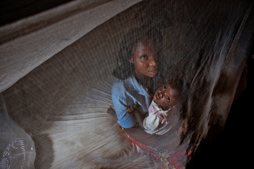 A woman and her little child under a mosquito net distributed by UMCOR in the Democratic Republic of Congo as part of the Imagine No Malaria program