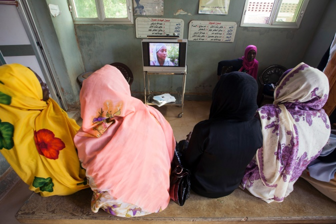 11 September 2013. El Fasher: Women watch a video campaign on HIV at the waiting room of the Women's Hospital in El Fasher, North Darfur. The video story was produced by the Ministry of Health of North Darfur to prevent the disease among the population. The official rate of HIV in Darfur is quite low (less than 1%), but experts think this rate is really higher because many people, mainly in the rural areas, has never been tested before.  Photo by Albert Gonz‡lez Farran, UNAMID.