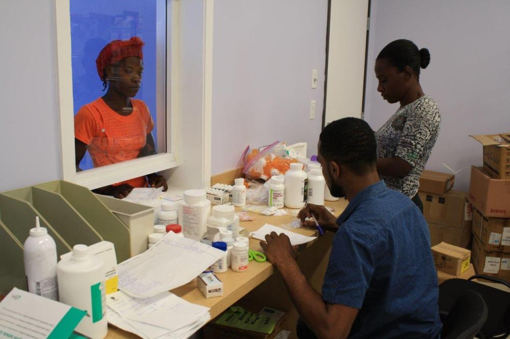 A patient at the hospital picks up her medication from Demar and Darcelin Jean at the pharmacy. (1)
